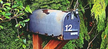 Altmodischer Briefkasten vor einer Hecke