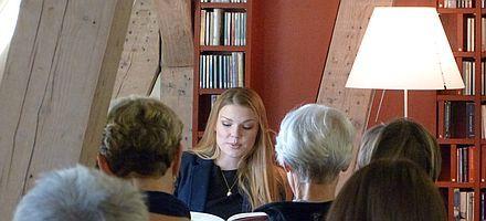 Eine Frau liest einigen Menschen aus einem Buch vor