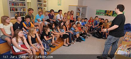 Ein Mann steht vor einer Gruppe sitzender Kinder und hält einen Vortrag