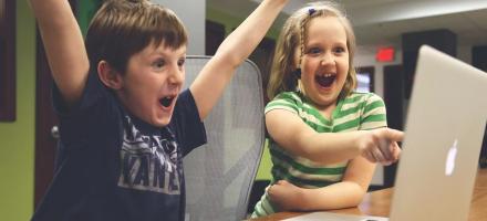 Einige kleine Kinder sitzen auf einer Bank und blicken in die selbe Richtung