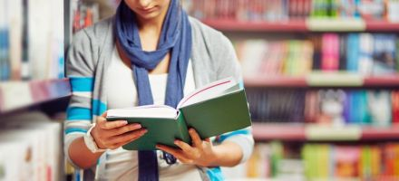 Eine Frau lehnt an einem Bücherregal und hält ein geöffnetes Buch in den Händen
