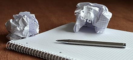Notziblock mit Stift und zerknülltem Papier