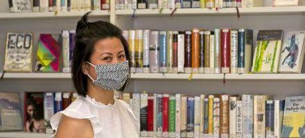 Junge Frau mit Mund-Nasen-Bedeckung vor Bücherregal
