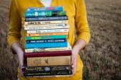 Eine Frau hält einen Stapel Bücher