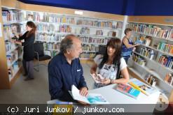 Ein Mann und eine Frau unterhalten sich vor Bücherregalen