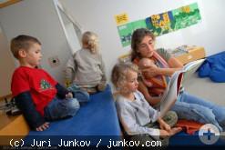 Eine Frau liest Kindern aus einem Buch vor