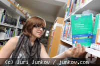 Eine junge Frau holt ein Buch aus einem Regal