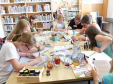 Am Tisch sitzende, malende Mädchen